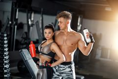 Fitness girl and guy model with a shaker relax in the gym. Slim sporty woman and man in sportswear clothes stock image