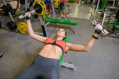Fitness girl at the gym with dumbbells. The concept of health, sports Stock Photography