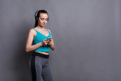 Fitness girl in headphones choose music on phone Stock Photo