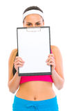 Fitness girl hiding behind blank clipboard. Isolated on white Stock Images