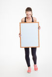 Fitness girl holding blank board and looking on it Royalty Free Stock Photography