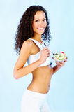 Fitness girl holding fresh salad. Portrait of a pretty fitness girl holding fresh salad on plate Royalty Free Stock Photo
