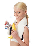 Fitness girl holding water bottle and banana Royalty Free Stock Image