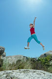 Fitness girl jumping over rocks Royalty Free Stock Photos