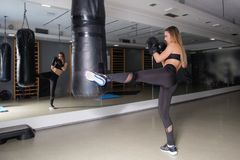 Fitness girl kicking at punching bag Royalty Free Stock Photo