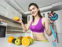 Fitness Girl on the Kitchen. Fitness girl near kitchen table with fruit and meter, keeping fit with healthy diet concept royalty free stock photo