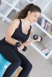 Fitness girl lifting dumbbells in front tv program. Fitness girl lifting dumbbells in front of tv program Stock Photography