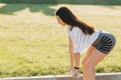 fitness girl making exercises with dumbbells on sunset at grass royalty free stock photo