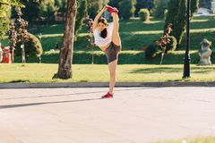 fitness girl making stretching at park at morning sunshine stock photography