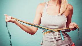 Fitness girl measuring her body with tapes stock photo
