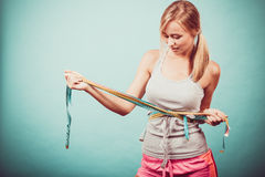 Fitness girl measuring her body with tapes royalty free stock images