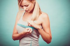 Fitness girl measuring her breasts royalty free stock photography