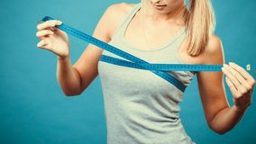 Fitness girl measuring her breasts stock image