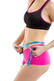 Fitness girl measuring her perfect shaped beautiful waist. She lost weight, with white background Stock Image