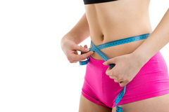Fitness girl measuring her perfect shaped beautiful waist. Royalty Free Stock Photos
