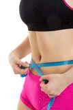 Fitness girl measuring her perfect shaped beautiful waist. She lost weight, with white background Stock Photography