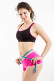 Fitness girl measuring her perfect shapeed beautiful waist. She lost weight, with white background Royalty Free Stock Photo