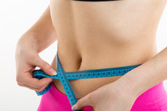 Fitness girl measuring her perfect shapeed beautiful waist. She lost weight, with white background Stock Images