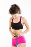 Fitness girl measuring her perfect shapeed beautiful waist. Royalty Free Stock Images