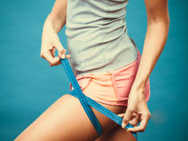 Fitness girl measuring her thigh royalty free stock photography