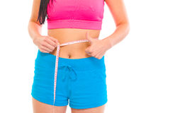 Fitness girl measuring her waist. Close-up. Fitness girl measuring her waist and showing thumbs up gesture isolated on white. Close-up Royalty Free Stock Images