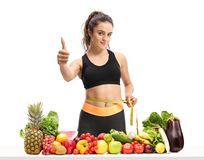 Fitness girl measuring her waist with a measuring tape and makin. G a thumb up sign behind a table with fruit and vegetables isolated on white background Royalty Free Stock Image