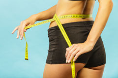 Fitness girl measuring her waistline Royalty Free Stock Images