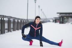 Fitness girl model runner doing flexibility exercise for legs before run at snow winter promenade Royalty Free Stock Photo