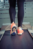 Fitness girl with muscular legs running on treadmill Royalty Free Stock Photography