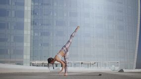 Woman doing downward facing dog pose. Girl performing yoga exercises on street