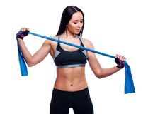 Fitness girl performs exercises with resistance band. Attractive young woman doing exercises with expander over white background. Royalty Free Stock Image