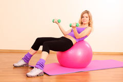 Fitness girl with pink ball. Young beautiful fitness girl with pink ball exercising in the gym stock image