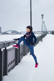Fitness girl with pink sneakers doing stretching outside at snow winter day, sport concept Stock Photos