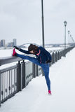 Fitness girl with pink sneakers doing stretching outside at snow winter outdoor Stock Photos