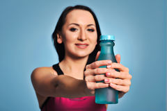 Fitness girl in pink top showing a bottle Royalty Free Stock Photography