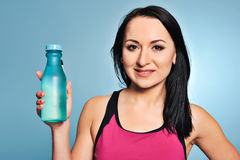 Fitness girl in pink top showing a bottle Royalty Free Stock Image