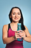 Fitness girl in pink top showing a bottle Royalty Free Stock Images