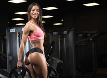 Fitness girl posing in the gym. Fitness girl with a beautiful smile posing in the gym stock photography