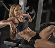 Fitness girl posing in the gym. Muscular fitness girl with a beautiful smile posing in the gym Stock Images