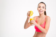 Fitness girl pressing orange juice into a glass Royalty Free Stock Images