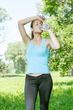 Fitness girl refreshment. Drinking water in the park Stock Photography