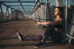 Fitness girl resting after workout. Young sport girl holding bottle of water and resting after workout. Stay hydrated royalty free stock image