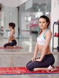 Fitness girl resting on a yoga mat in a gym. Fitness young woman sitting on a yoga mat in a gym Stock Photography