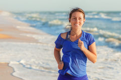 Fitness girl running on the beach Royalty Free Stock Images