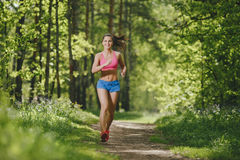 Fitness girl running on forest trail and smiling Royalty Free Stock Photo