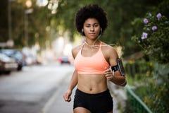 Fitness girl running on sidewalk, enjoying music. Stock Image