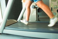 Fitness girl running on treadmill. Woman in gym Stock Photo