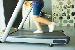 Fitness girl running on treadmill. Woman in gym Stock Image