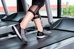 Fitness girl running on treadmill, Woman with muscular legs in g. Close up sneakers Fitness girl running on treadmill, Woman with muscular legs in gym stock photo
