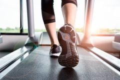 Fitness girl running on treadmill, Woman with muscular legs in g. Close up sneakers Fitness girl running on treadmill, Woman with muscular legs in gym Royalty Free Stock Photos